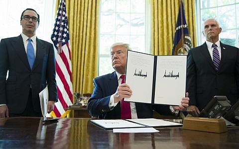 US President Donald Trump holds up a signed executive order to increase sanctions on Iran, in the Oval Office of the White House, June 24, 2019, in Washington. Trump is accompanied by Treasury Secretary Steve Mnuchin, left, and Vice President Mike Pence. (AP Photo/Alex Brandon)