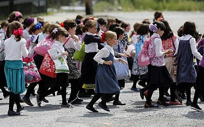 Illustrative: Girls walk to waiting buses after summer day camp on July 1, 2014, in Kiryas Joel, New York (AP Photo/Mike Groll)