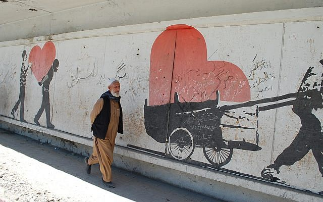 An Afghan man in Kabul passes a mural near the site of a deadly bombing, upon which are scrawled slogans reading, 'Death to Israel.' (Ezzatullah Mehrdad/ Times of Israel)