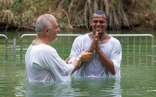 Houston Texans all-star quarterback Deshaun Watson (right) getting baptized in the Jordan River, June 19, 2019. (American Voices in Israel)