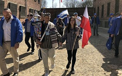 Edward Mosberg, holding a Torah scroll, during March of the Living in 2017 at the former death camp Auschwitz in Poland. (Courtesy of From the Depths via JTA)