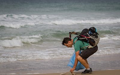 Israeli blogger Gil Drori picked up plastic bag on the Beit Yanai beach on November 23, 2018, during his 9-day journey to raise awareness of the harmful effects of disposable plastic pollution on the Mediterranean Sea. (Meir Vaknin/Flash90)