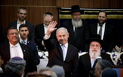 Prime Minister Benjamin Netanyahu waves to the crowd during a Jerusalem Day celebration at Mercaz HaRav Yeshiva in Jerusalem, on June 2, 2019. To his right is Jerusalem Mayor Moshe Lion. (Aharon Krohn/Flash90)
