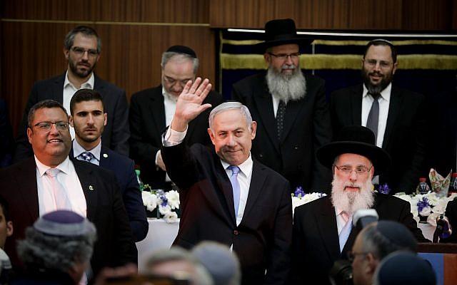Prime Minister Benjamin Netanyahu waves to the crowd during a Jerusalem Day celebration at Mercaz HaRav Yeshiva in Jerusalem, on June 2, 2019. To his right is Jerusalem Mayor Moshe Lion. (Aharon Krohn/Flash90)