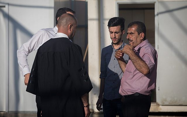 Attorney Nashaf Darwish (L) speaks with the brother and son of Mahmoud Qadusa, a Palestinian man charged with kidnapping and raping a 7-year-old Israeli girl, at the Judea Military Court in the West Bank on June 19, 2019. (Yonatan Sindel/Flash90)