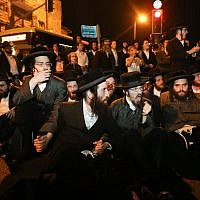 Ultra-Orthodox Jewish men block a road during a protest against the arrest of ultra-Orthodox Jewish women who failed to comply with a recruitment order, in Jerusalem, June 24, 2019. (Noam Revkin Fenton/Flash90)