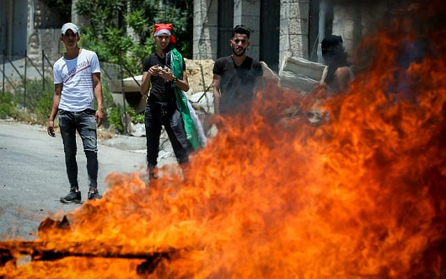 Palestinian demonstrators clash with Israeli border police during a protest against US President Donald Trump's economic plan, in the West Bank village of Halhoul, near Hebron, on June 24, 2019. (Wisam Hashlamoun/Flash90)