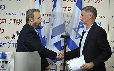 Former prime minister Ehud Barak (L) shakes hands with Yair Golan after announcing the formation of a new party at Tel Aviv's Beit Sokolov on June 26, 2019. (Jacob Magid/Times of Israel)