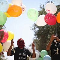 Illustrative: Palestinians prepare balloon-borne incendiary devices to launch at Israel, at the Bureij refugee camp in the Gaza Strip on May 31, 2019. (Hassan Jedi/Flash90)
