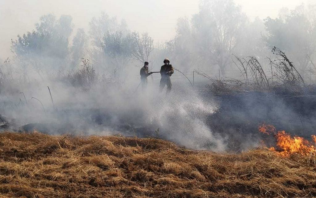 Firefighters battle a brushfire in southern Israel near the Gaza border that was started by an incendiary device launched from the Gaza Strip on June 24, 2019. (Yankele Grossfeld/Sha'ar Hanegev Regional Council)