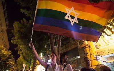 A woman waves a Jewish Pride flag in Jerusalem on August 1, 2015. (Omer Messinger/NurPhoto via Getty Images via JTA)