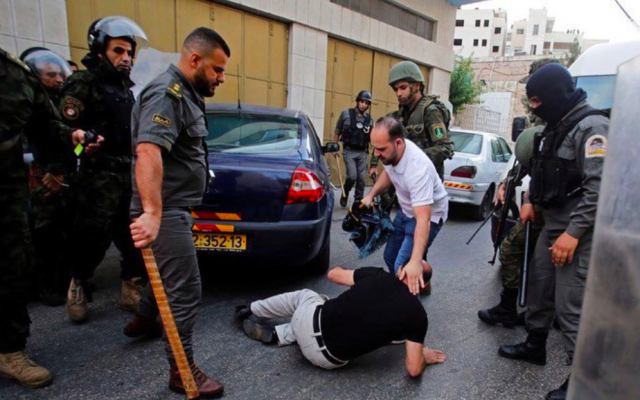 Palestinian Authority security forces surrounding who appears to be a supporter of Hizb al-Tahrir in Hebron on June 4, 2019. (Screenshot: Twitter)