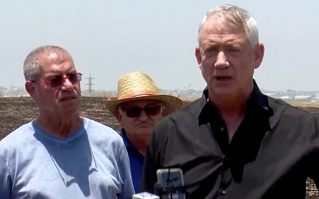 Blue and White party leader Benny Gantz (R) speaks to reporters at a burnt field in southern Israel on June 28, 2019. (Screen capture: Twitter)