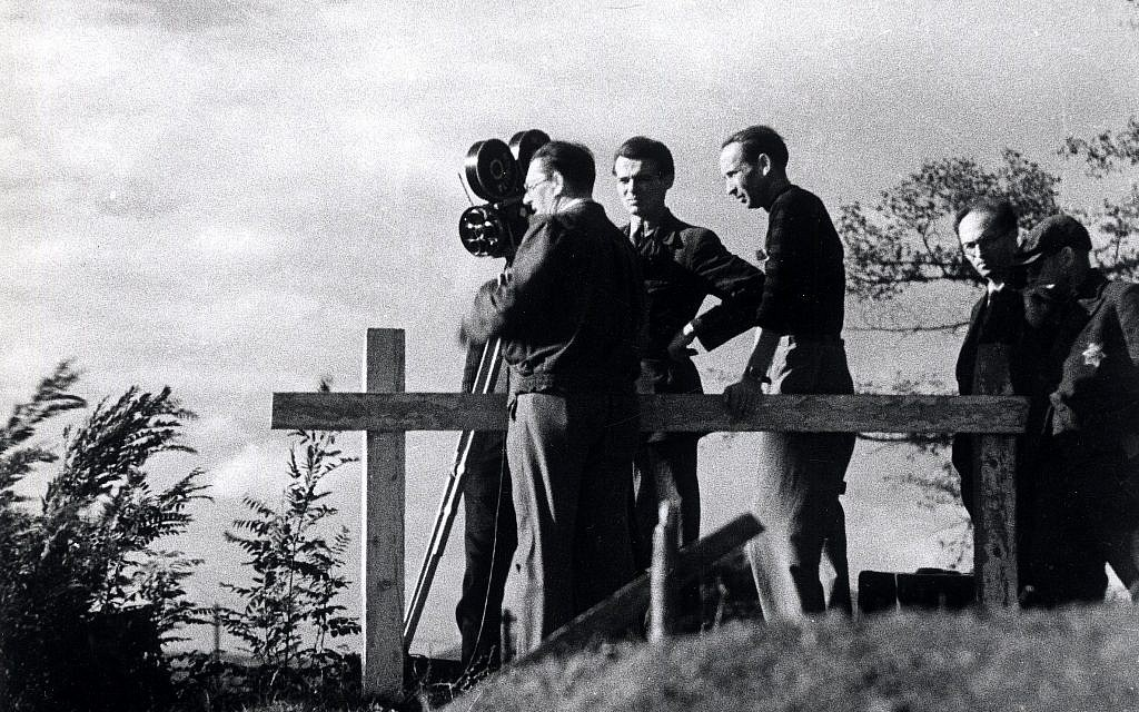 A film crew takes motion pictures in the Theresienstadt ghetto during the filming of a Nazi propaganda film in 1944. A Jewish assistant wearing a Star of David is on the right. (Public domain)
