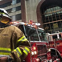 A New York City firefighter responds to the scene where a helicopter crash-landed on the roof of a midtown Manhattan skyscraper, June 10, 2019, in New York. (AP Photo/Mark Lennihan)