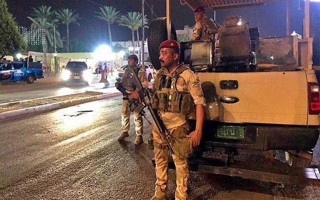 Iraqi security forces stand guard near the Bahraini embassy in Baghdad, Iraq, after protesters stormed the compound to protest the US-led peace conference hosted by Bahrain earlier in the week. June 27, 2019. (AP/Ali Abdul Hassan)