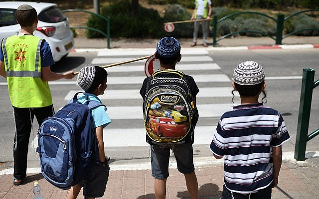 School children standing in front of a crosswalk after leaving school in Beit El, May 1, 2019. (Gili Yaari /Flash90)