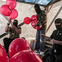 Palestinians prepare incendiary balloons near the city of Jabalia in the Gaza Strip, June 25, 2019. (Hassan Jedi/Flash90)