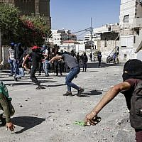 Palestinians throw stones during clashes with Israeli police in Jerusalem's neighborhood of Issawiya on June 28, 2019, a day after a Palestinian was shot and killed by police during a protest in the same neighborhood. (Hazem Bader/AFP)