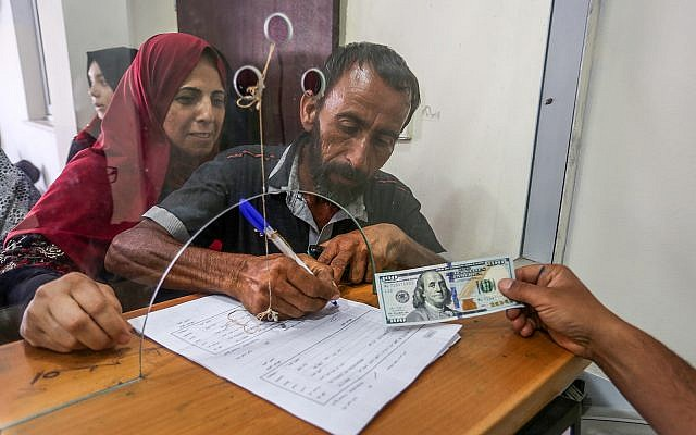 Palestinians receive financial aid from Qatar at a post office in Gaza City, June 20, 2019. (Abed Rahim Khatib/Flash90)