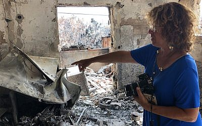 Zelda Burkey points to what remains of her home in Mevo Modi'im, which was destroyed along with much of the village in a fire in May 2019. (Sam Sokol/JTA)