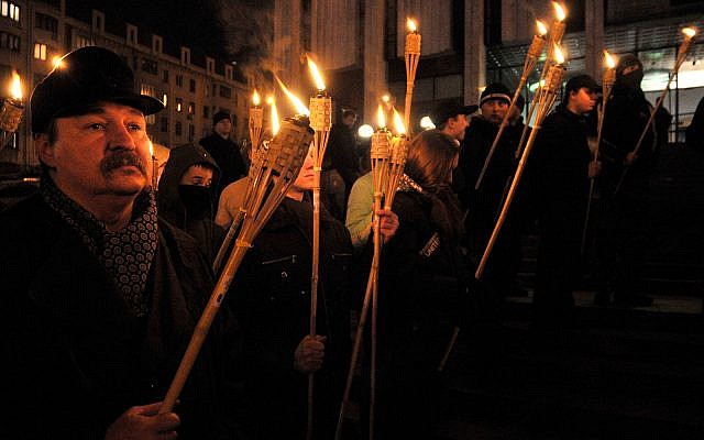 Ukrainians hold burning torches as they gather in Kiev, Ukraine, March 5, 2010, to mark the 60th anniversary of the death of Roman Shukhevych, a Ukrainian politician, military leader and Nazi collaborator. (AP Photo/Sergei Chuzavkov)