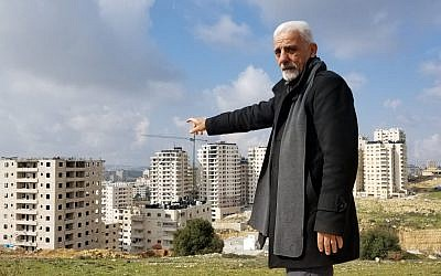 Munir Zughayer, an activist who leads a committee that frequently complains to the Jerusalem Municipality about the state of services in Kafr Aqab, points to a number of buildings that were built in contravention of regulations on February 20, 2019. (Adam Rasgon/Times of Israel)