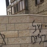 """A village of terrorists"" is spray-painted on a wall in the Palestinian village of Sinjil on June 24, 2019. (Jamal Asfour)"