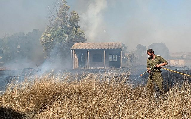 A military firefighter works to extinguish a blaze caused by an incendiary device from the Gaza Strip in a field in the Sha'ar Hanegev region of southern Israel on June 27, 2019. (Sha'ar Hanegev regional council)