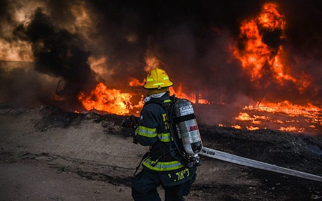 A firefighter works to extinguish a blaze caused by an incendiary device from the Gaza Strip in southern Israel on June 27, 2019. (Fire and Rescue Services)