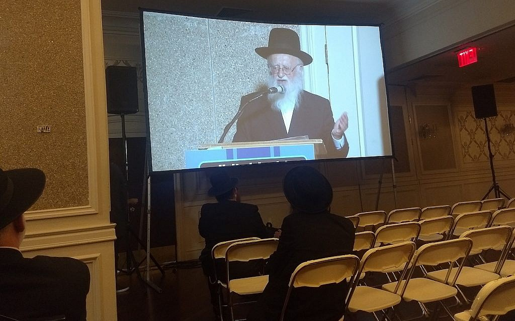Rabbi Hillel Handler, an Orthodox anti-vaccination leader, speaks via projection screen to an anti-vaccination rally in Brooklyn at a Jewish wedding hall, June 4, 2019. (Ben Sales/JTA)