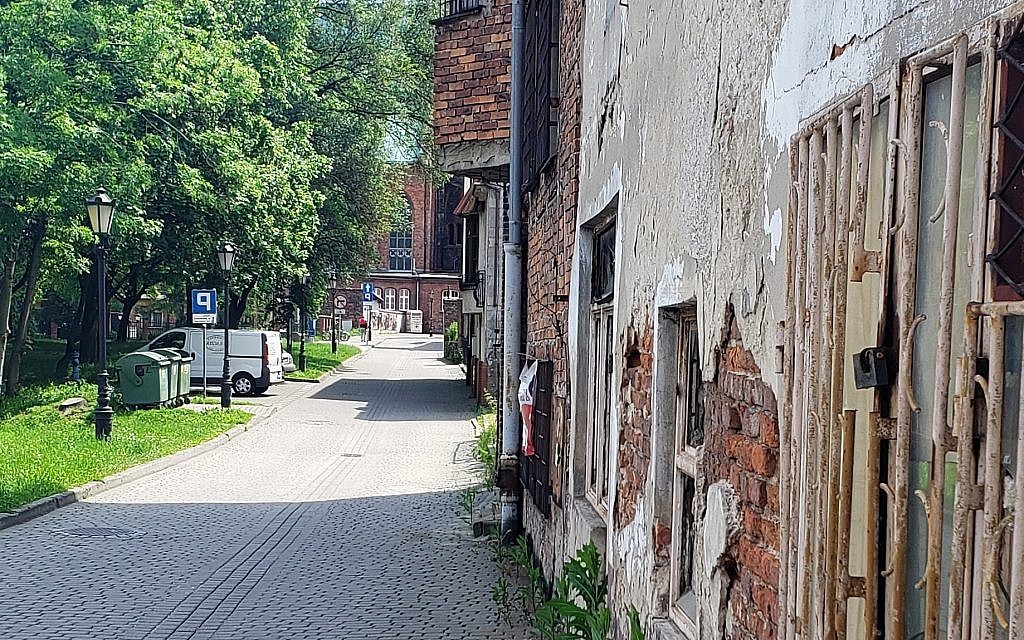 Former 'Jewish Street' in Oswiecim, Poland; the facade of the Great Synagogue was located near the grass, May 2019 (Matt Lebovic/The Times of Israel)