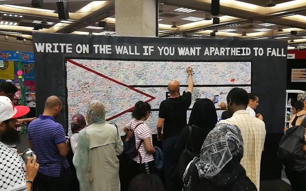 Attendees at Palestine Expo 2017 in London write on a wall to protest Israeli 'apartheid.' (Screenshot YouTube)