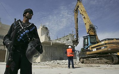 Illustrative: Israeli police stand near an excavator as it demolishes a Palestinian home in the East Jerusalem neighborhood of Sur Baher on April 7, 2009. (Kobi Gideon/Flash90)