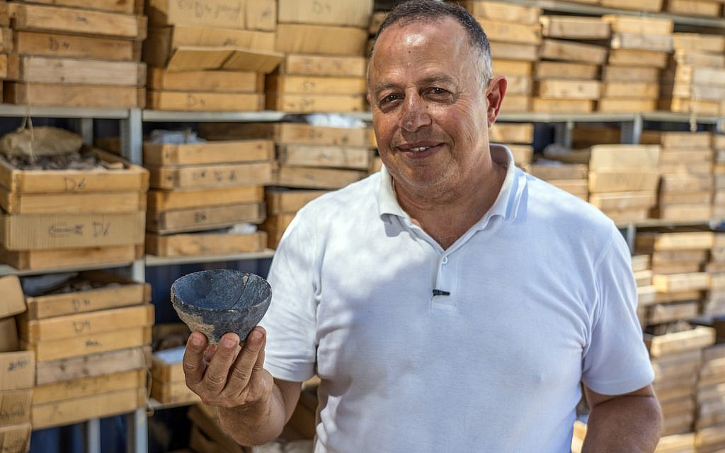 Dr. Hamoudi Khalaily, Antiquities Authority Excavation director at the Motza site, holding a bowl from the Neolithic Period. (Yaniv Berman, Israel Antiquities Authority)
