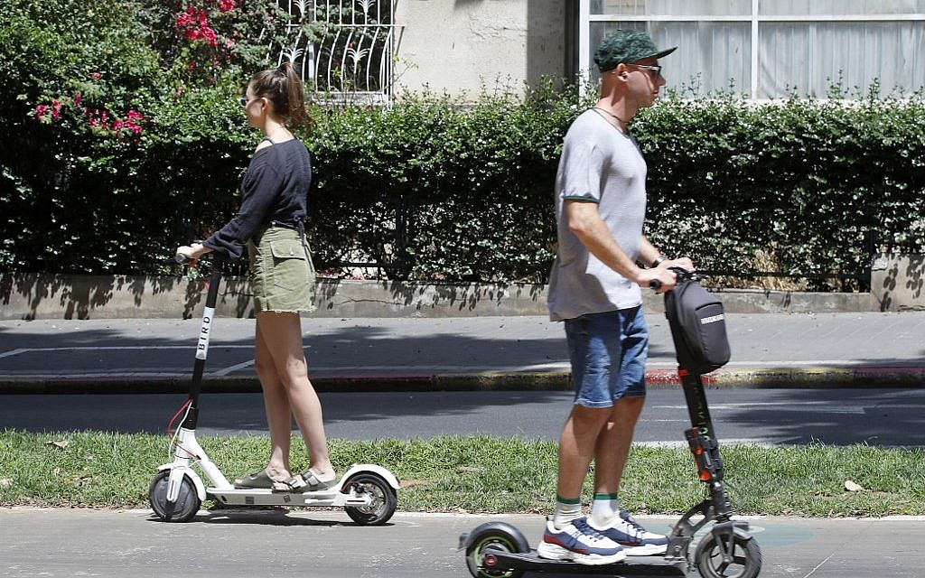 People ride electric scooters in the streets of the Israeli coastal town of Tel Aviv on May 30, 2019 (JACK GUEZ / AFP)
