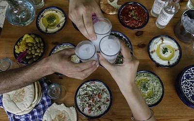 Palestinian distiller Nader Muaddi drinks his handcrafted arak in the West Bank city of Beit Jala, near Bethlehem, on June 16, 2019. (HAZEM BADER/AFP)