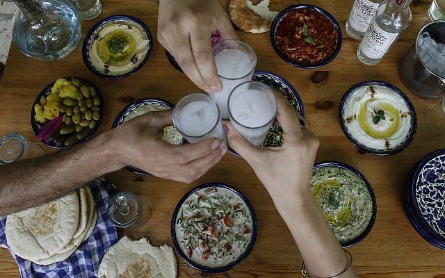 Palestinian distiller Nader Muaddi drinks his handcrafted arak in the West Bank city of Beit Jala, near Bethlehem, on June 16, 2019. (HAZEM BADER/AFP)