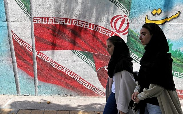 Iranian women walk past a mural painted with the Iranian flag in Tehran on June 25, 2019. (ATTA KENARE / AFP)
