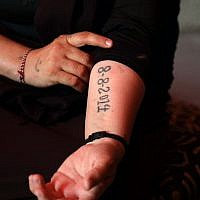 An Iraqi Yazidi survivor displays a tattoo bearing the date fighters from the Islamic State group entered the village of Sinjar, at her tent in the Khonke camp for displaced persons in northwestern Iraq on June 24, 2019. (SAFIN HAMED/AFP)