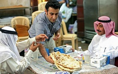 A waiter serves Iranian bread - known as taftoon - at the Al-Walimah restaurant in Kuwait City on June on June 27, 2019. - Iranian bread has for decades been a staple of Kuwaiti breakfast, lunch and dinner tables. For Kuwaitis, their bond with Iranian culture remains unchanged despite the growing regional tensions between the Sunni-ruled Gulf countries and the Shiite Islamic republic. (Photo by Yasser Al-Zayyat / AFP)