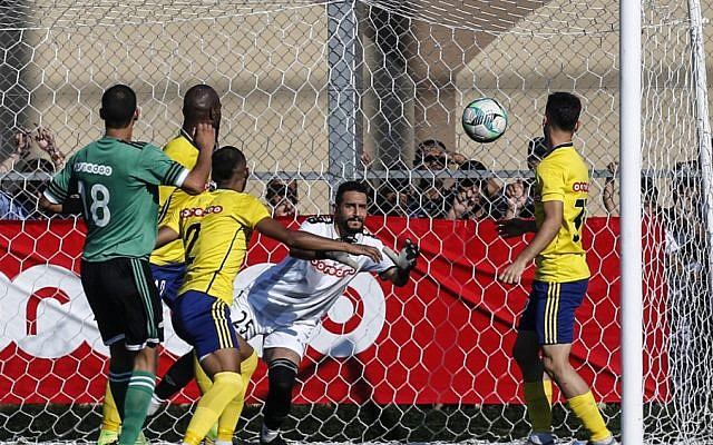Khadamat Rafah Club's goalkeeper leaps to save the ball during the during a game in Rafah in the southern Gaza Strip on June 30, 2019. (SAID KHATIB / AFP)