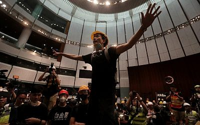 A protester gestures after they broke into the parliament chamber of the government headquarters in Hong Kong on July 1, 2019, on the 22nd anniversary of the city's handover from Britain to China.  (VIVEK PRAKASH / AFP)