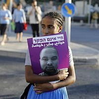 An Israeli woman holds a poster of Solomon Tekah, a young man of Ethiopian origin who was killed by an off-duty police officer, as members of the Israeli Ethiopian community block the main entrance to Jerusalem on July 2, 2019 to protest his killing. (MENAHEM KAHANA / AFP)