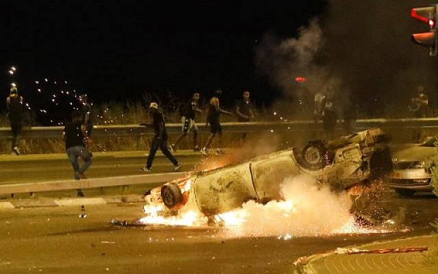 A police car burns as members of the Ethiopian community in Israel clash with the police during in the Israeli coastal city of Netanya on July 2, 2019, during a protest against the killing of Solomon Tekah, a young man of Ethiopian origin, who was killed by an off-duty police officer.(Photo by JACK GUEZ / AFP)