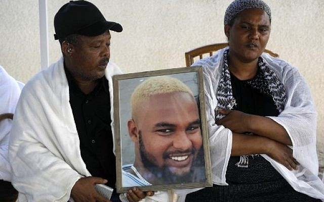 Worka  and Wbjig Tekah hold a picture of their son Solomon Tekah, 19, who was killed by an off duty police officer on July 1, 2019, at their home in the Israeli city of Haifa on July 3, 2019. (MENAHEM KAHANA / AFP)