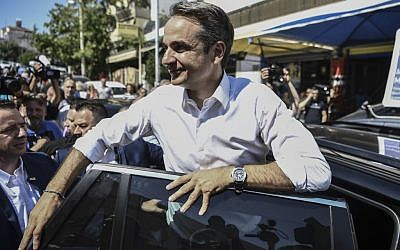 Greece's opposition party New Democracy leader Kyriakos Mitsotakis (C) greets supporters as he leaves a polling station after casting his vote during general elections in Athens on July 7, 2019. (Aris MESSINIS / AFP)