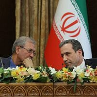 A handout picture provided by the Iranian presidency on July 7, 2019 shows (L to R) Iran's government spokesman Ali Rabiei and Deputy Foreign Minister Abbas Araghchi speaking to each other during a joint press conference at the presidential headquarters in the capital Tehran on July 7, 2019.  )Iranian Presidency / AFP)