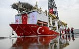 Journalists walk next to the drilling ship 'Yavuz' scheduled to search for oil and gas off Cyprus, at the port of Dilovasi, outside Istanbul, on June 20, 2019. (BULENT KILIC / AFP)