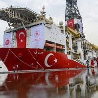Journalists walk next to the drilling ship 'Yavuz' scheduled to search for oil and gas off Cyprus, at the port of Dilovasi, outside Istanbul, on June 20, 2019. (Bulent Kilic/AFP)